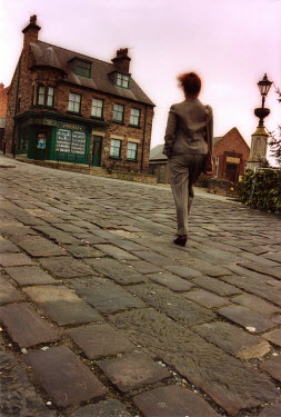 Michael Trevillion WOMAN WALKING ON STONE PAVED ROAD Women