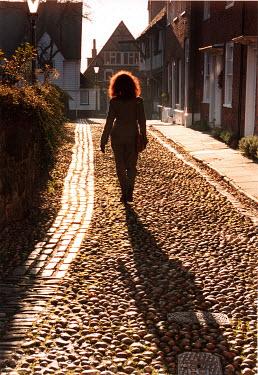 Michael Trevillion WOMAN WALKING ON COBBLESTONE STREET Women