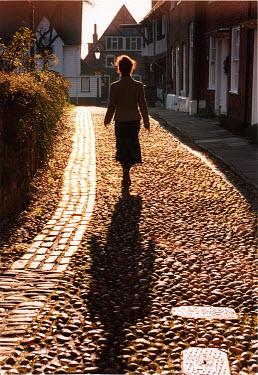 Michael Trevillion WOMAN WALKING IN COBBLE STREET Women