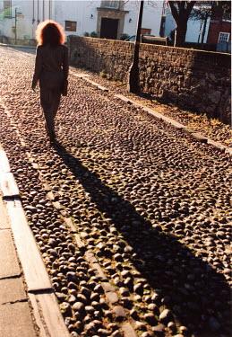Michael Trevillion WOMAN WALKING ON COBBLE ROAD Women