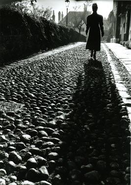 Michael Trevillion WOMAN WALKING ON COBBLESTONE ROAD Women