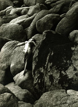 Graham Hughes WOMAN LAYING ACROSS ROCKS Women