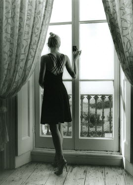 Lesley Aggar WOMAN LOOKING OUT OF BALCONY WINDOW Women