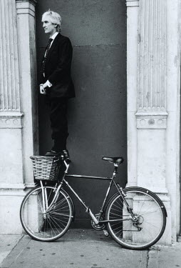David Gibson MAN STANDING ON FRONT OF BICYCLE Men