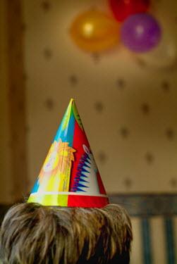 Adrian Muttitt BOY WEARING PARTY HAT Children