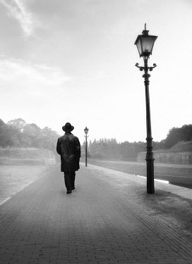 Yolande de Kort SILHOUETTE OF MAN IN HAT BY LAMP POSTS Men