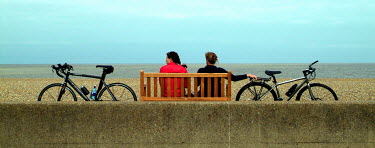 Adrian Muttitt COUPLE WITH BIKES ON BENCH Couples