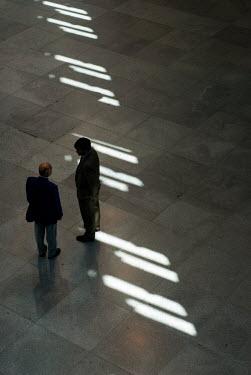 David Foster TWO MEN STANDING IN LARGE HALLWAY Men