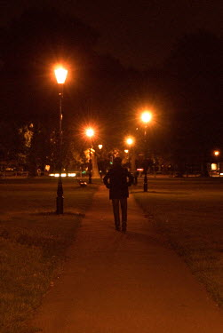 David Foster MAN WALKING THROUGH PARK AT NIGHT Men