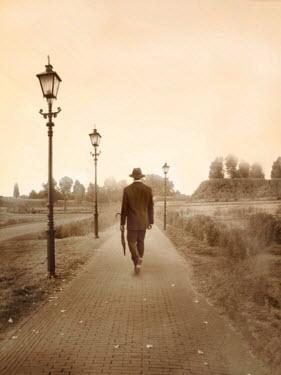Yolande de Kort RETRO MAN IN HAT WALKING PAST LAMP POSTS Men