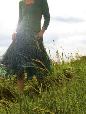 David Grogan WOMAN WALKING THROUGH FIELD Women
