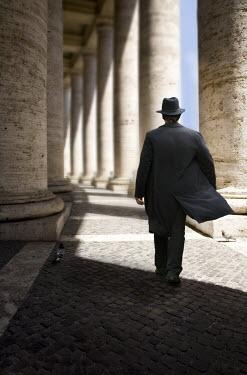 Yolande de Kort MAN IN HAT WALKING BESIDE STONE PILLARS Men