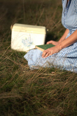 Hilary Walker WOMAN WITH BOOK AND RADIO ON GRASS Women