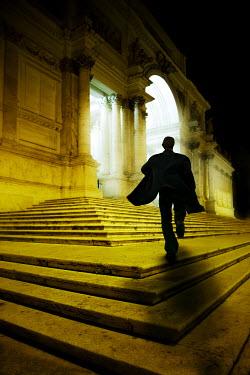 Yolande de Kort SILHOUETTE OF MAN RUNNING ON BUILDINGS STEPS Men