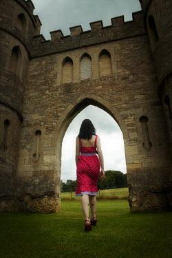 Emma Delves-Broughton WOMAN IN RED DRESS WALKING NEAR CASTLE Women