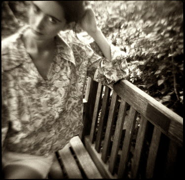 Christine Rodin WOMAN IN FLORAL SHIRT SITTING ON GARDEN BENCH Women