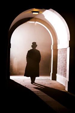 Neil Denham MAN WALKING THROUGH ARCHWAY Men