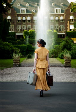 Yolande de Kort VINTAGE WOMAN WITH SUITCASES IN MANSION GARDENS Women
