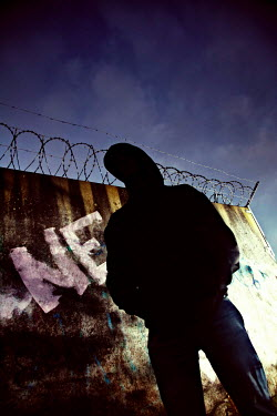 Andy & Michelle Kerry HIIDED FIGURE BY WALL WITH BARB WIRE Men