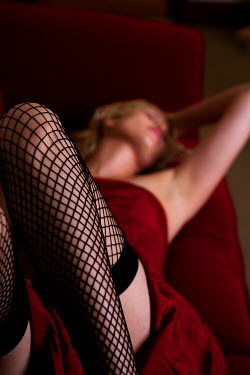 Nick Sokoloff WOMAN IN FISHNETS LAYING ON SOFA Women
