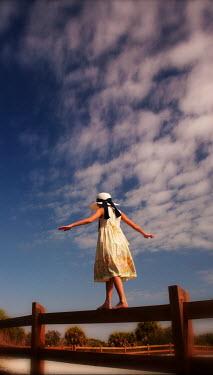 Terry Bidgood girl walks along wooden fence Children