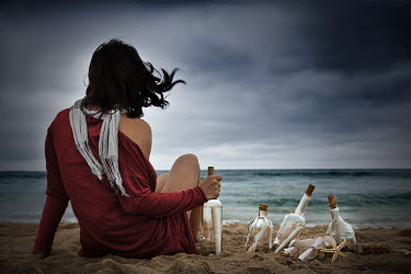 Alisa Andrei woman on beach with messages in bottles Women