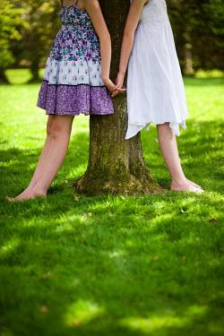 Lee Avison TWO GIRLS HOLDING HANDS LEANING AGAINST TREE Couples