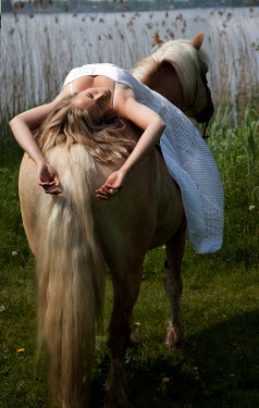 Yolande de Kort BLONDE WOMAN LYING ON PALOMINO HORSE Women
