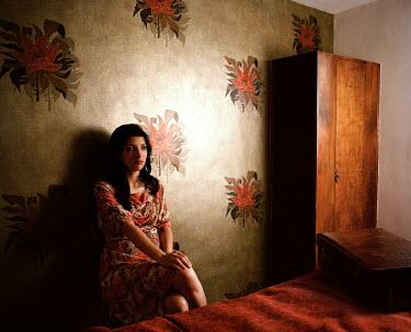 Rebecca Miller DARK HAIRED WOMAN SITTING IN BEDROOM Women