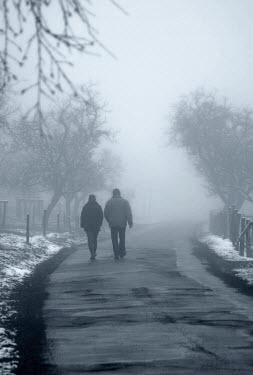 Ilona Wellmann COUPLE WALKING ALONG ROAD IN WINTER Couples