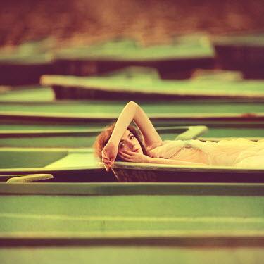 Oleg Oprisco WOMAN LYING IN WOODEN BOAT Women