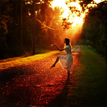 Masha Sardari WOMAN DANCING ON ROAD IN SUNSET Women