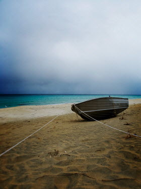 Douglas Black wooden boat on sandy beach Boats