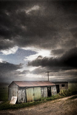 John Cooper DERELICT METAL BARN WITH STORMY SKY Miscellaneous Buildings
