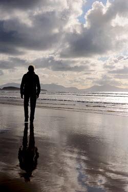 Clint Hughes MAN WALKING ON SHIMMERING BEACH Men