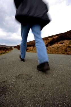 Clint Hughes Man walking along road Men