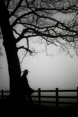Neil Denham MAN IN HAT LEANING BY TREE IN FOG Men