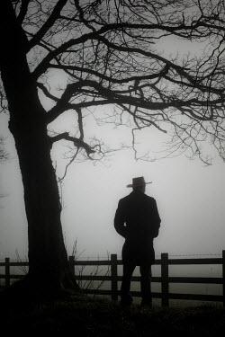 Neil Denham MAN IN HAT STANDING BY FENCE IN FOG Men