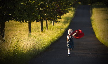 Jennifer Short BOY IN RED CAPE RUNNING IN COUNTRY ROAD Children