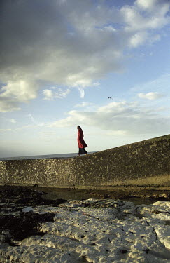 Richard Dunkley WOMAN WALKING ON SEA WALL Women