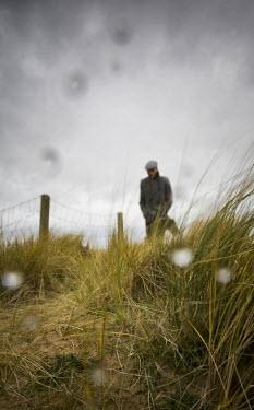 John Harrison MAN WALKING BY SAND DUNES IN WINTER Men