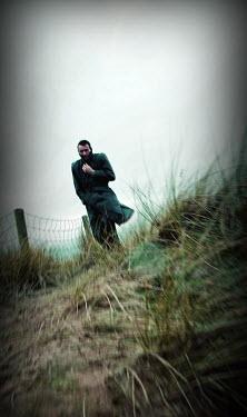 John Harrison MAN WALKING BY SAND DUNE IN WINTER Men