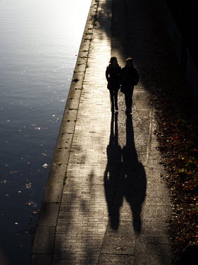 Richard Dunkley COUPLE WALKING BY RIVER IN SUNLIGHT Couples