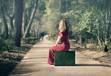 Laura Franco WOMAN SITTING ON SUITCASE ON PATH WITH MAN Couples