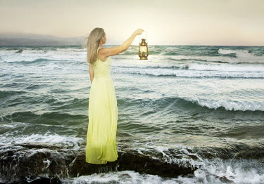 Laura Franco BLONDE WOMAN IN YELLOW DRESS HOLDING LANTERN BY SEA Women