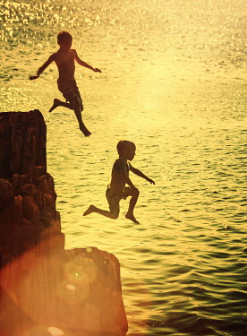 Elisabeth Ansley TWO BOYS JUMPING FROM ROCKS IN SEA Children