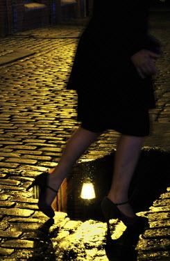Ute Klaphake LEGS OF WOMAN IN COBBLED STREET Women