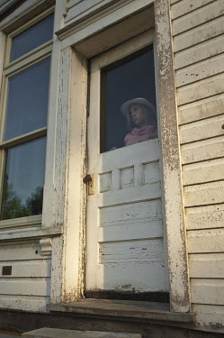 Terry Bidgood WOMAN STANDING AT DOOR OF WHITE WOODEN HOUSE Women