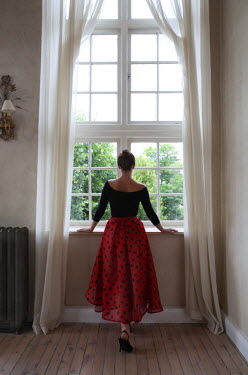 Lesley Aggar WOMAN IN RED BY WINDOW Women
