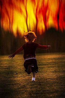 Elisabeth Ansley CHILD RUNNING OUTDOORS WITH SUNSET Children